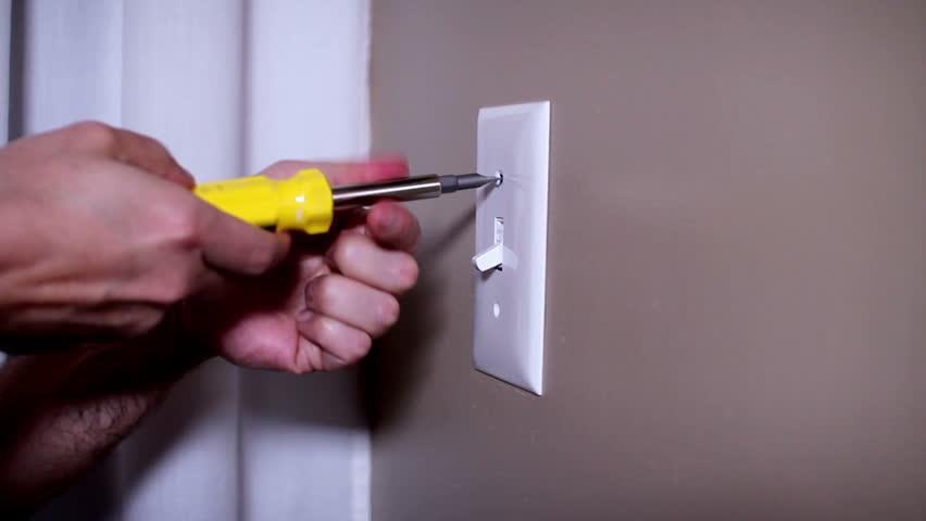 An electrician repairs a wall light switch. | Shutterstock HD Video #3685082