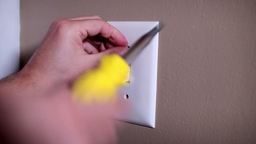 An electrician repairs a wall light switch. | Shutterstock HD Video #3685085