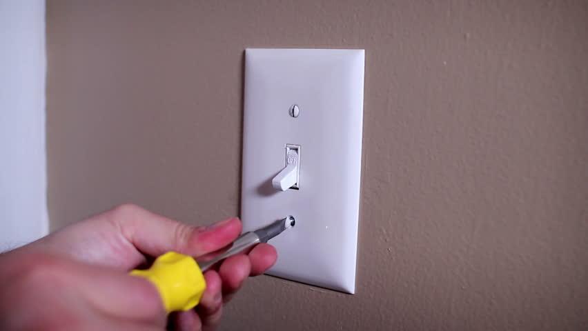 An electrician repairs a wall light switch. | Shutterstock HD Video #3685088