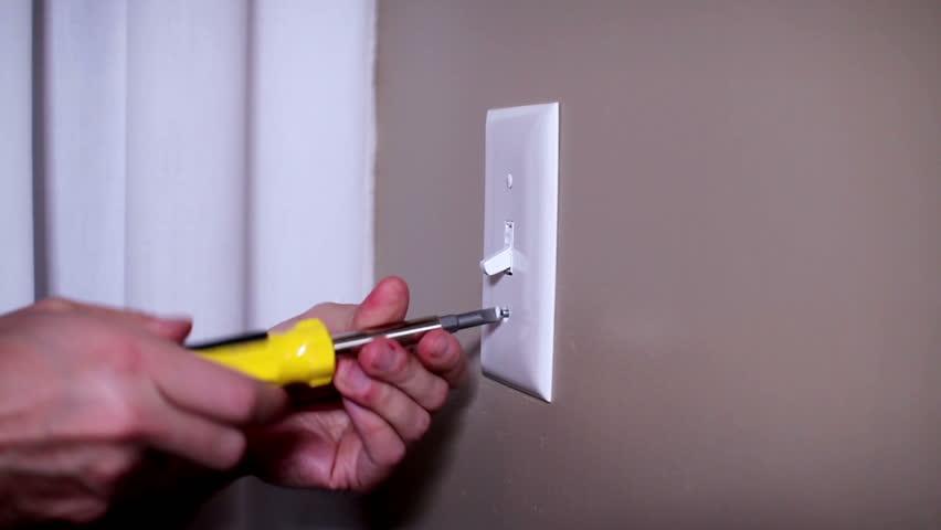 An electrician repairs a wall light switch. | Shutterstock HD Video #3685091