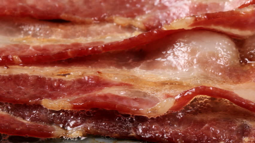 Extreme closeup pan of bacon cooking on a griddle #3697250