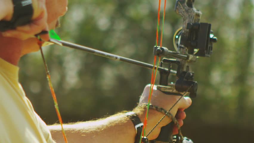 Slow motion shot of an archer firing an arrow from his compound bow toward a range target.