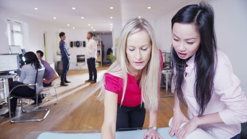 Two beautiful multi-ethnic businesswomen are working in a light and modern office and looking at a map of the world. They are discussing possibilities for future business ventures. In slow motion. | Shutterstock HD Video #3702710