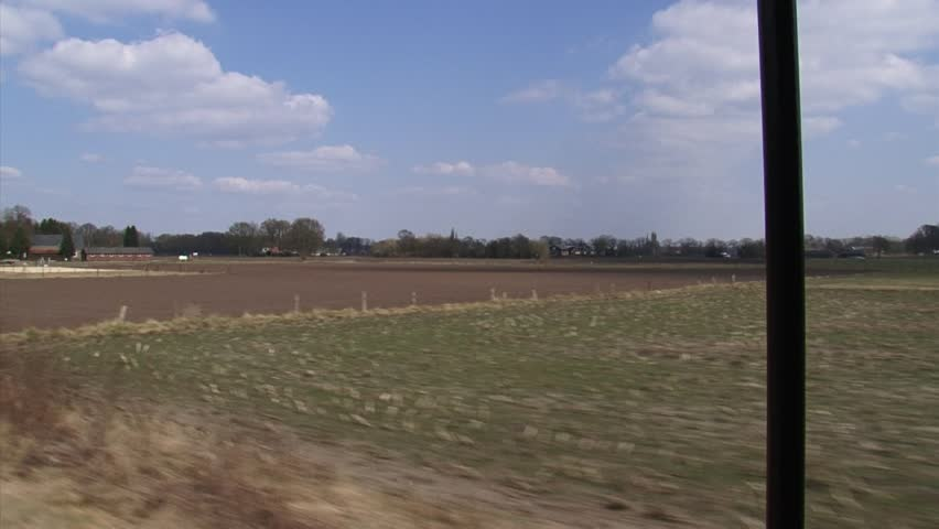 Vehicle shot from  train - passing a Dutch farm + rural landscape against a blue sky - early spring | Shutterstock HD Video #3708269