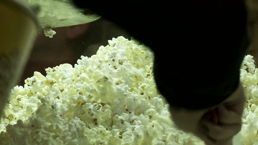 Close view of theater popcorn being served into a cardboard bucket.