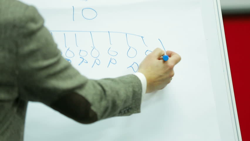 Lecturer drawing a scheme on a board during a seminar.