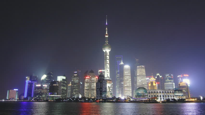 Time lapse of Shanghai skyline and tour boat passing in the Huangpu river at