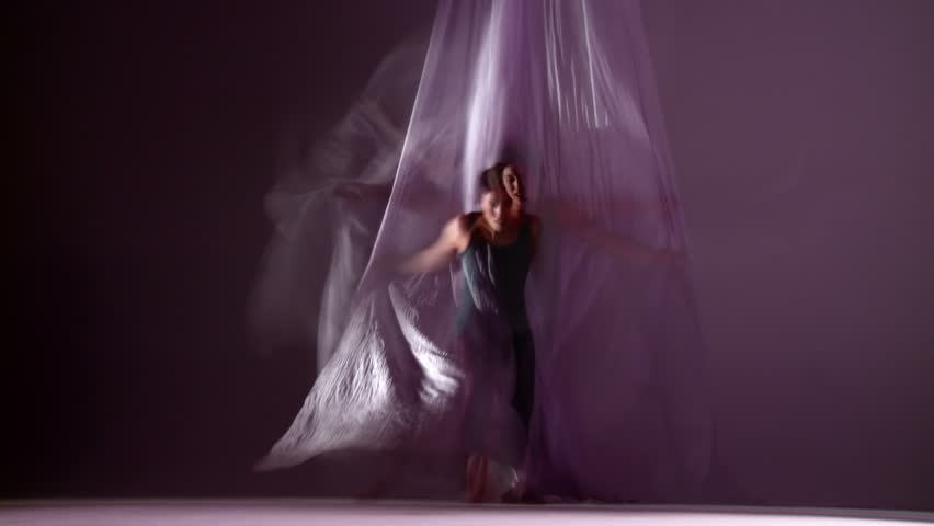 Gymnastic young woman dances with silks, runs towards camera. Composited with