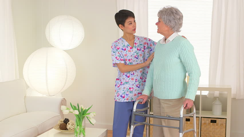 Chinese nurse aiding elderly patient