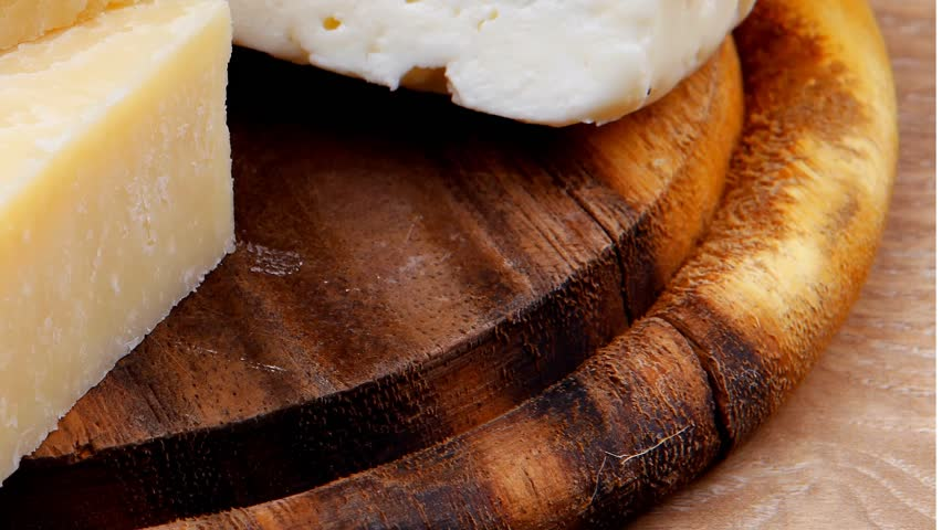 Various types of cheese on wooden platter over wooden table | Shutterstock HD Video #3769682