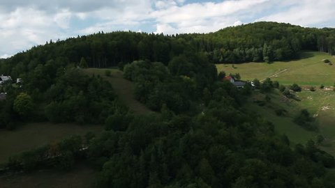 HD shot from helicopter of hill covered with forest and meadow