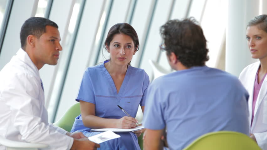 Group of doctors and nurses having conversation seated around table. Shot on Canon 5d Mk2 with a frame rate of 30fps