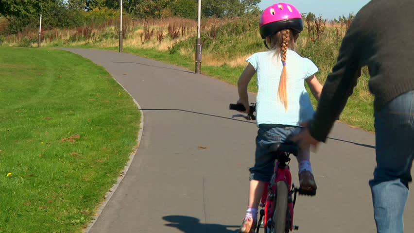 Little girl learning to ride her bicycle with help from her dad - dolly | Shutterstock HD Video #3787487