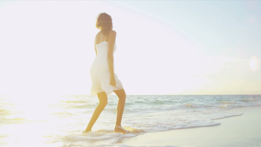 Pretty girl in sundress reveling being alone by ocean at sunrise on beach vacation sun, lens flare shot on RED EPIC