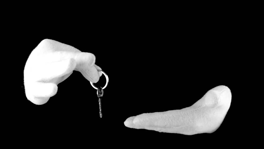 Black background. White-gloved hands manipulated with the key on the ring