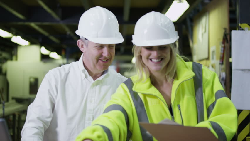 A happy team of workers in a warehouse or factory are going about their business and preparing goods for delivery. One male staff member is checking the inventory on a laptop computer. In slow motion. | Shutterstock HD Video #3808070