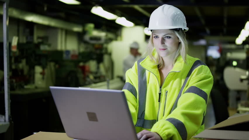 A beautiful female warehouse employee wearing high visibility clothing and a hard hat is working on a laptop computer and checking her stock. | Shutterstock HD Video #3808268