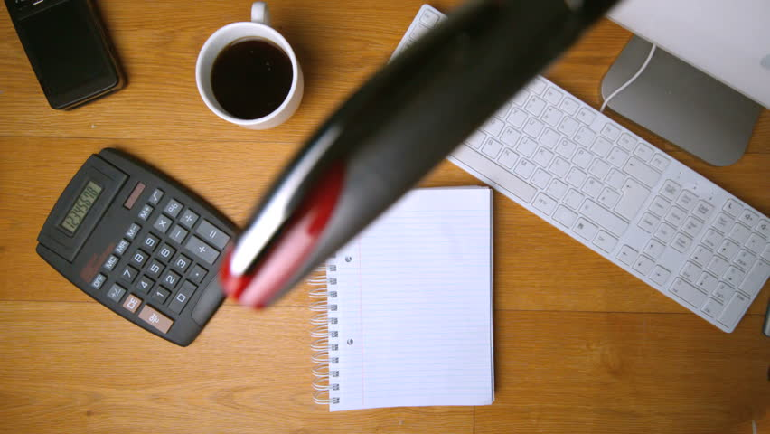 Fountain pen falling onto notepad on office desk beside computer calculator and coffee in slow motion | Shutterstock HD Video #3808517