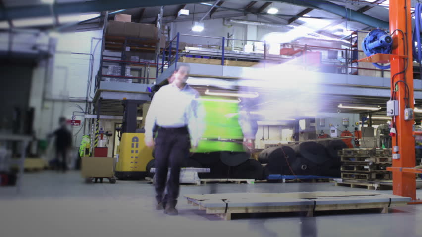 Time-lapse clip of busy workers in a warehouse or factory, wearing high visibility clothing and hard hats. They are checking stock levels and using a forklift truck to move empty wooden pallets.