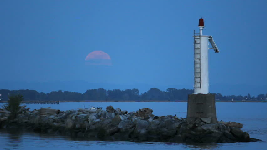 Moonrise Fraser, River, Steveston. A full moon rises over the Fraser River by the entrance to Steveston Harbor. British Columbia, Canada, near Vancouver.