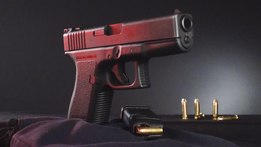 Semi-automatic Pistol in focus as it rotates.