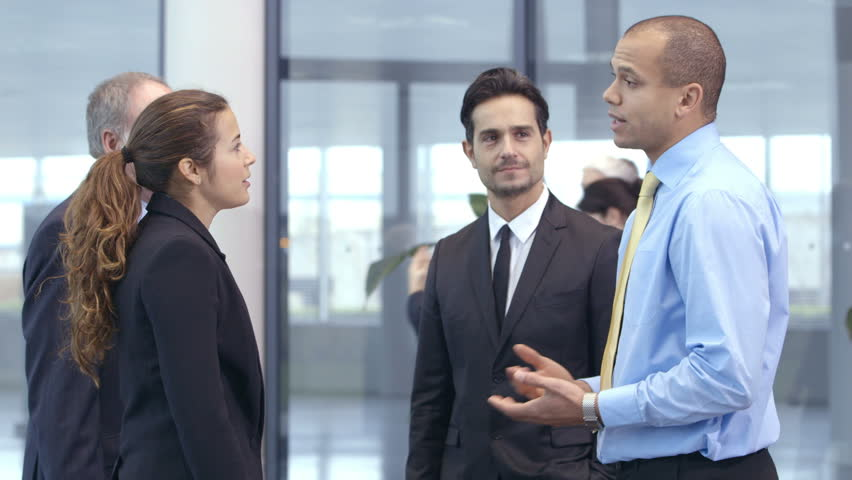 Confident and attractive business team of mixed ages and ethnicity meet and shake hands in the lobby of a busy modern office building.  | Shutterstock HD Video #3848735