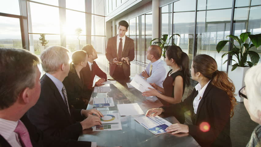 A confident and attractive business team of mixed ages and ethnicity are holding a meeting in a light, modern office building. They are discussing ideas for their business development.