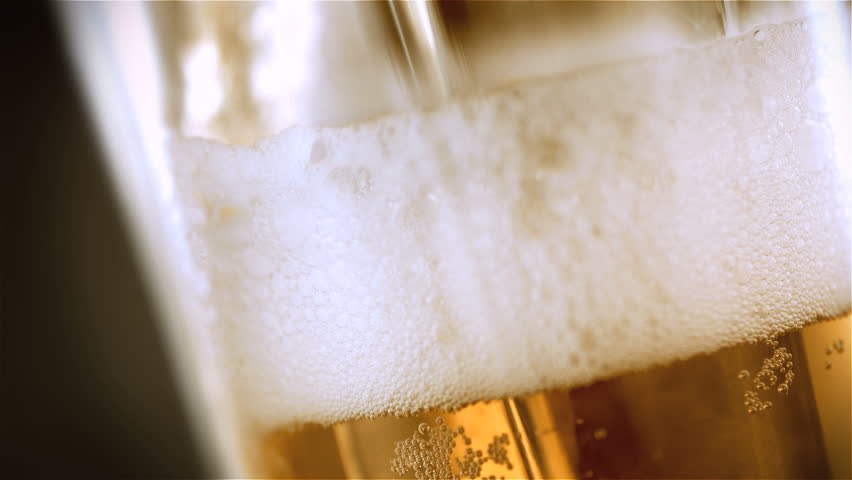 Beer is pouring into the angled glass. | Shutterstock HD Video #3849902