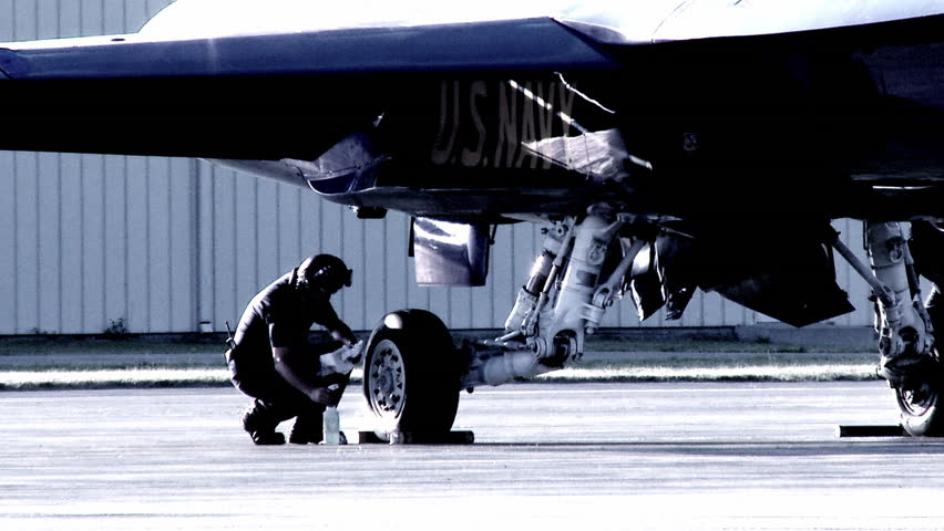 Aircrew cleaning the wheels on an F-18 Hornet fighter plane.