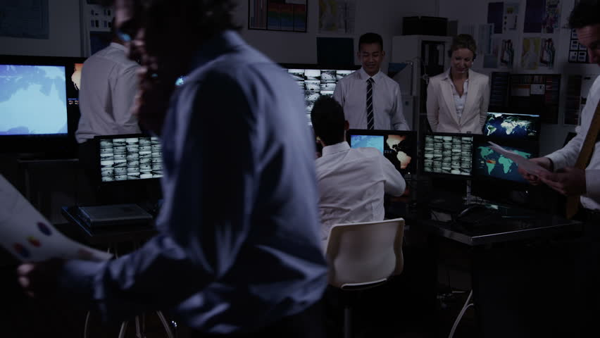 A team of security personnel working in a busy system control room, could be a weather station/airport traffic control. It could be a  power station or police/army control facility. In slow motion. #3857957
