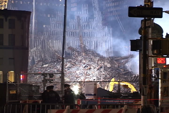 NEW YORK CITY - SEPTEMBER 28, 2001: Smoke rising from floodlit rubble with remains of World Trade Center structure in background.