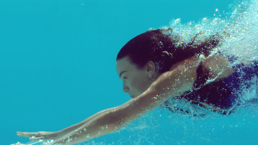 Woman swimming underwater in slow motion