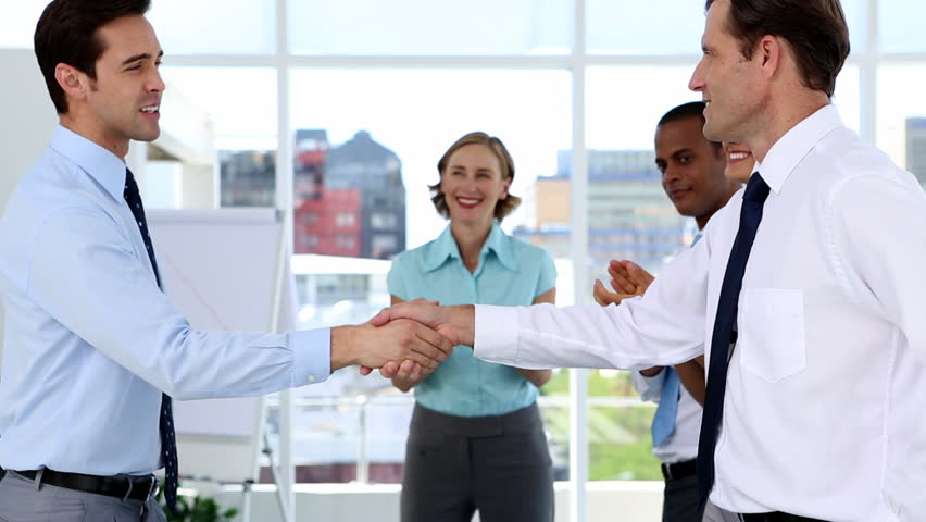 Side view of smiling Caucasian businessmen shaking hands while other multi-ethnic business people applauding in bright office