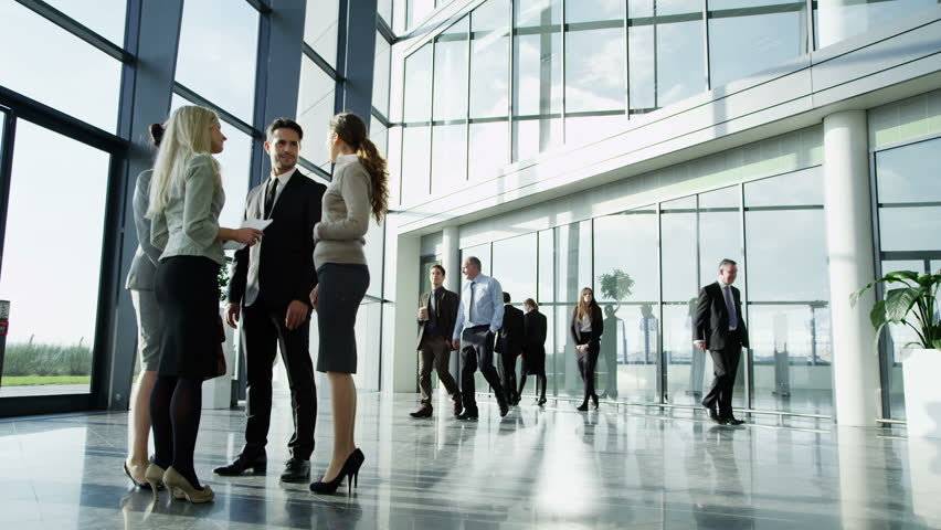An attractive young business team are having a conversation in a bright modern office building. Other workers in the building walk past them as they chat. In slow motion. | Shutterstock HD Video #3893450
