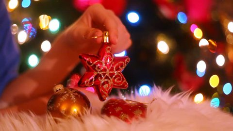 Hand holding a star shape globe in front of christmas tree