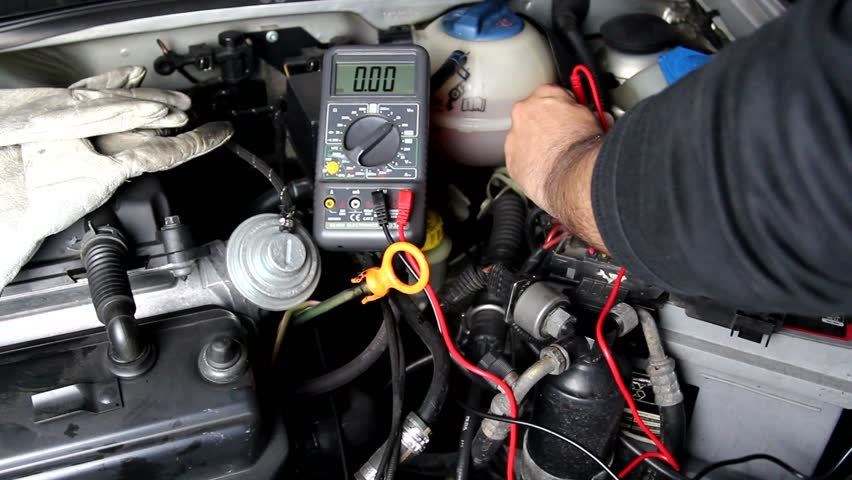 Mechanic uses a digital multimeter to check the voltage #3918605