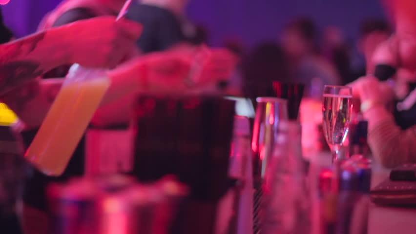Bartender serving drink for visitors, orange juice and vodka alcohol
