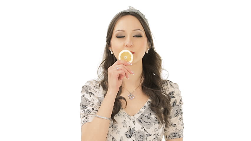 Lovely young woman making expression after tasting a slice of bland lemon  | Shutterstock HD Video #3929186