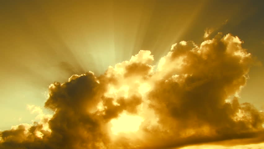 Beautiful yellow cloudscape with large, building clouds and sunrise breaking