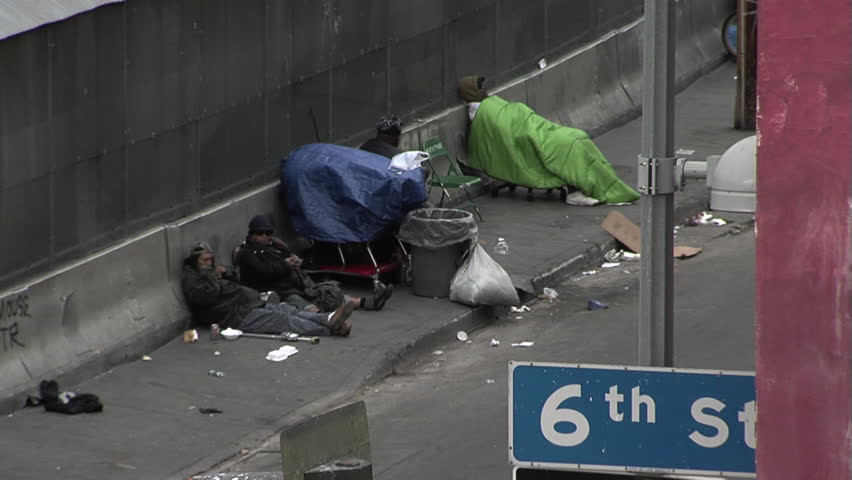 LOS ANGELES, CA - CIRCA MARCH 2012 - Skid Row in Los Angeles across from the Midnight Mission.  Homeless people sitting on the sidewalk with their belongings trying to stay warm.