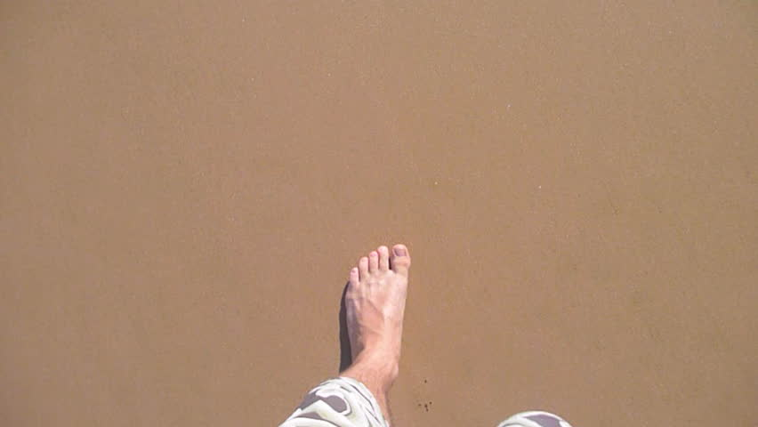 Man walking bare foot on sandy beach into ocean wave, point of view.
