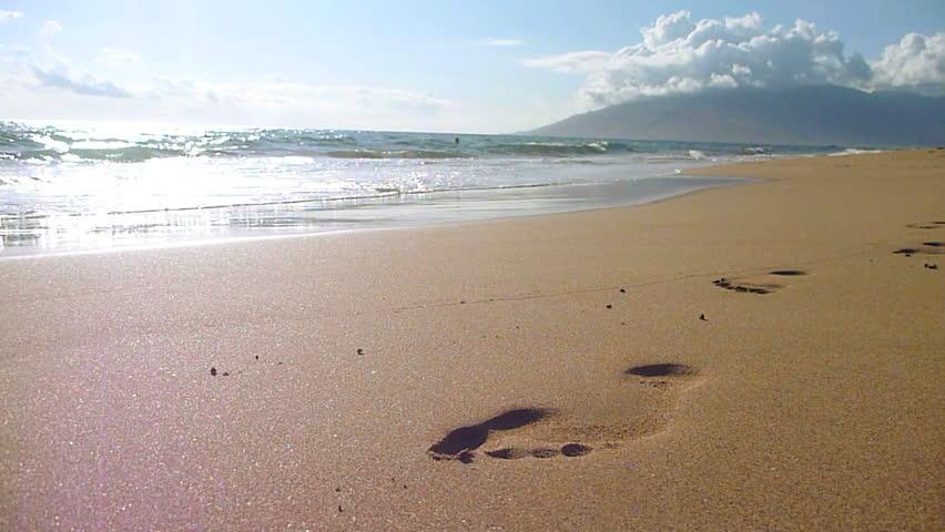 Waves crashing on shore wipe away footprint in the sand on beach in Hawaii.