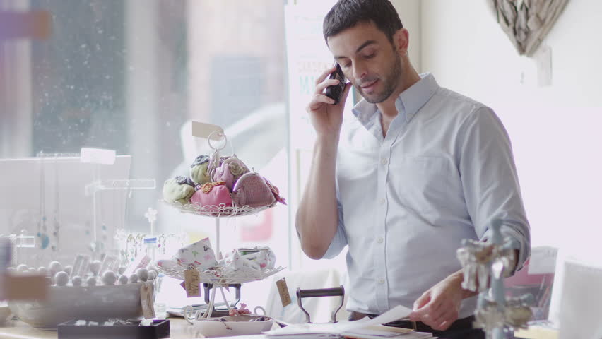 An attractive male store owner makes a phone call at work, possibly to his suppliers or a business associate. In slow motion.