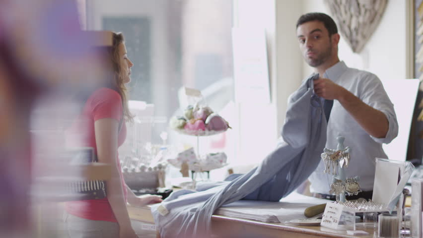 An attractive male store assistant or business owner chats to his female customer as he serves her. In slow motion.