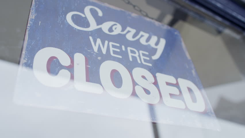 'Open' sign is turned to 'Closed' in a storefront window
