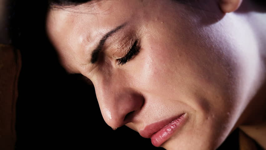 Depressed woman crying alone in the dark