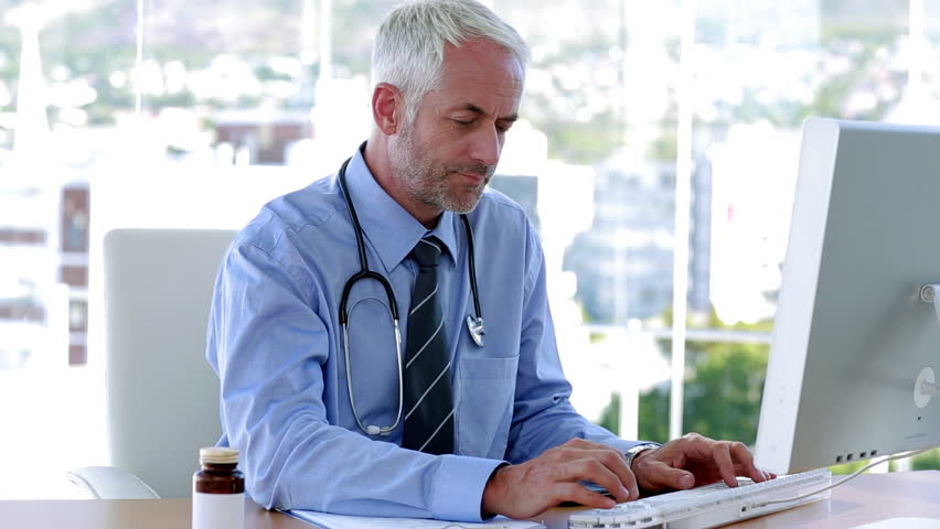 Smiling doctor working in office on his computer | Shutterstock HD Video #3997672