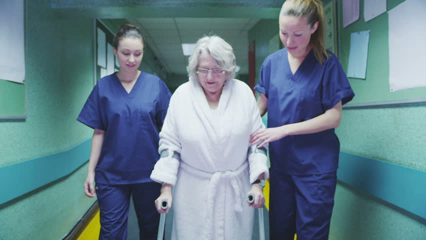 Two attractive female medical assistants help an elderly lady on crutches to take a walk down the hospital corridor. In slow motion.