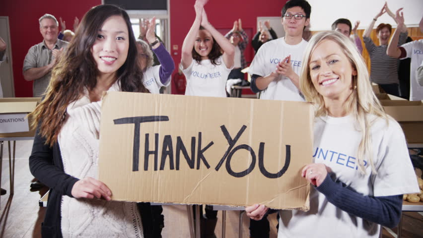 """Two attractive female charity volunteers of Caucasian and Asian ethnicity hold up a """"Thank You"""" sign and smile into the camera. Their fellow volunteers applaud and cheer in the background.Slow motion. Royalty-Free Stock Footage #4024906"""