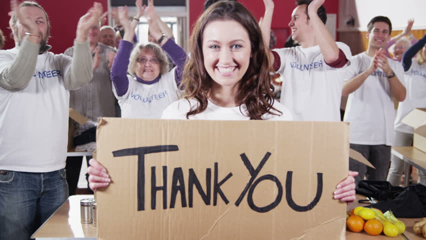 """An attractive female charity volunteer holds up a """"Thank You"""" sign and smiles at the camera as her fellow volunteers applaud and cheer in the background. Royalty-Free Stock Footage #4027942"""